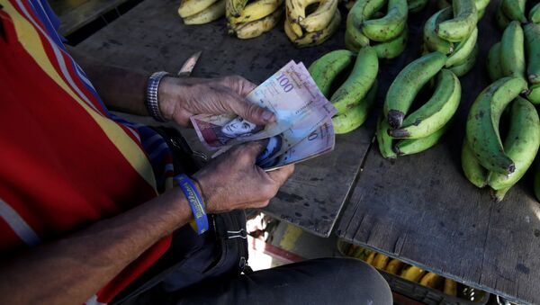 A vendor counts Venezuelan bolivar notes at his stall in a street market in the slum of Petare in Caracas, Venezuela - Sputnik Mundo
