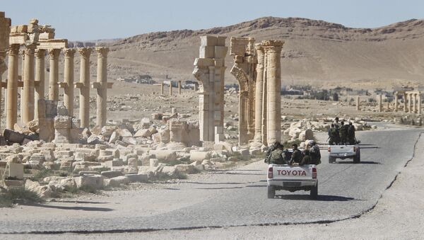 Syrian army soldiers drive past the Arch of Triumph in the historic city of Palmyra, in Homs Governorate, Syria - Sputnik Mundo