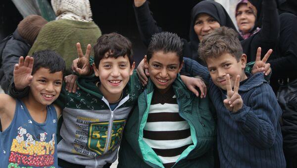 Niños que celebran la liberación en Hanano, este de Alepo - Sputnik Mundo