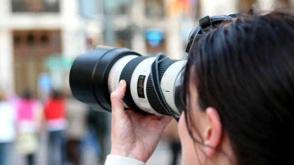Una mujer con cámara (imagen referencial) - Sputnik Mundo
