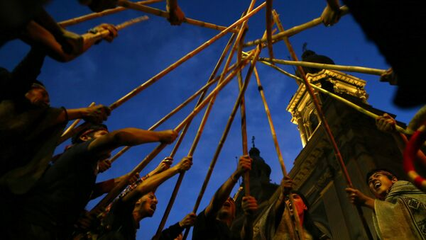Mapuche Indian activists raise their sticks during a demonstration to demand justice for indigenous Mapuche inmates as well as for their indigenous rights and land for their communities in Santiago - Sputnik Mundo