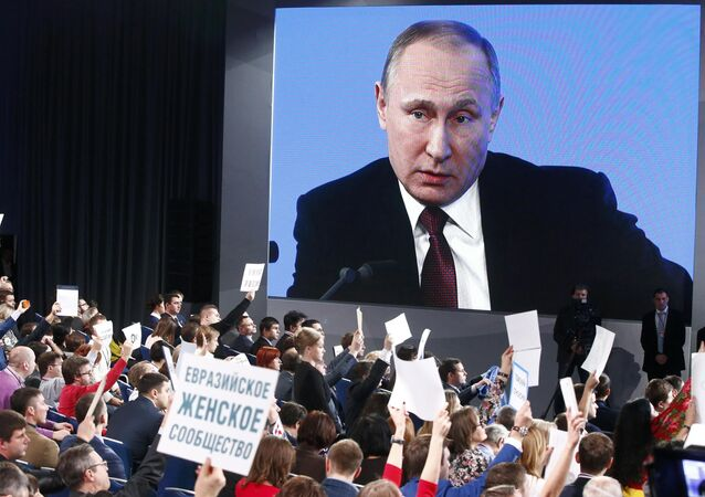 Journalists listen to Russian President Vladimir Putin during his annual end-of-year news conference in Moscow, Russia