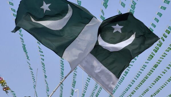 Pakistanis wave national flags - Sputnik Mundo