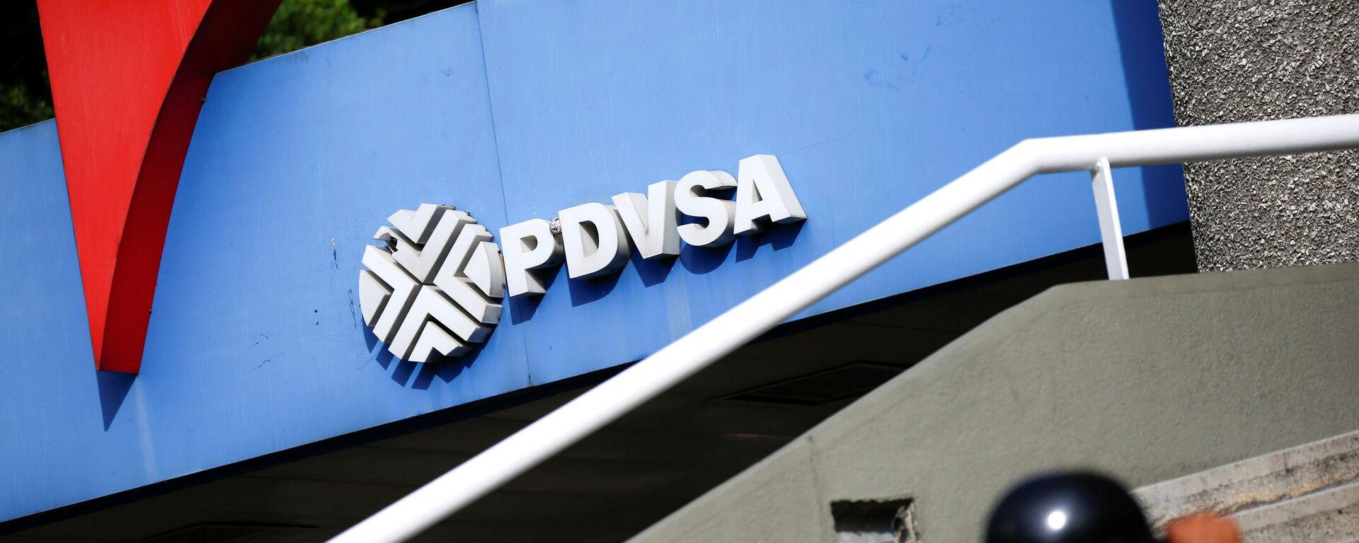 A man walks past a gas station with the logo of the Venezuelan state oil company PDVSA in Caracas, Venezuela December 23, 2016. REUTERS/Carlos Garcia Rawlins - Sputnik Mundo, 1920, 22.04.2021
