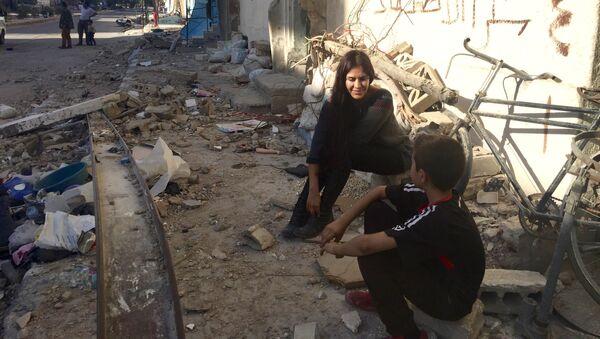 La cineasta boliviana Carla Ortiz junto a un niño en Siria - Sputnik Mundo