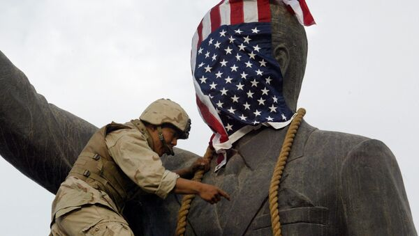 A US Marine covers the head of a statue of Iraqi President Saddam Hussein with the US flag before pulling it down in Baghdad's al-Fardous (paradise) square 09 April 2003 as the marines swept into the Iraqi capital and the Iraqi leader's regime collapsed. - Sputnik Mundo