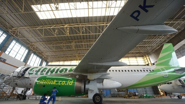 This picture taken on April 4, 2013 in Tangerang shows Indonesian technicians from GMF (Garuda Maintenance Facilities), a subsidiary of national carrier Garuda Indonesia maintaining a Citilink - Sputnik Mundo