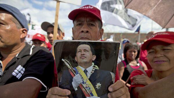Un simpatizante del presidente Nicolás Maduro sostiene un retrato del expresidente venezolano Hugo Chávez - Sputnik Mundo