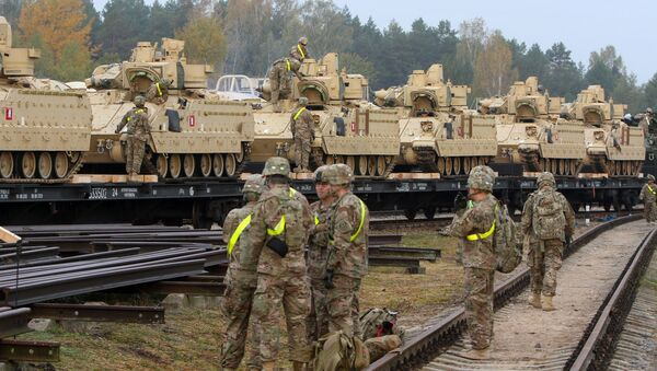 Members of the US Army 1st Brigade, 1st Cavalry Division, unload heavy combat equipment including Bradley Fighting Vehicles at the railway station near the Rukla military base in Lithuania, on October 4, 2014 - Sputnik Mundo