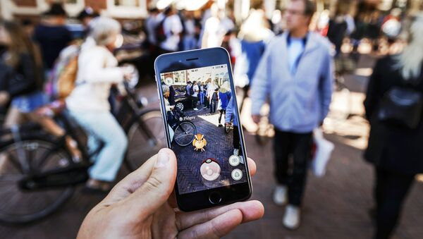 Gamers play with the Pokemon Go application on their mobile phone, at the Grote Markt in Haarlem, on July 13, 2016 - Sputnik Mundo
