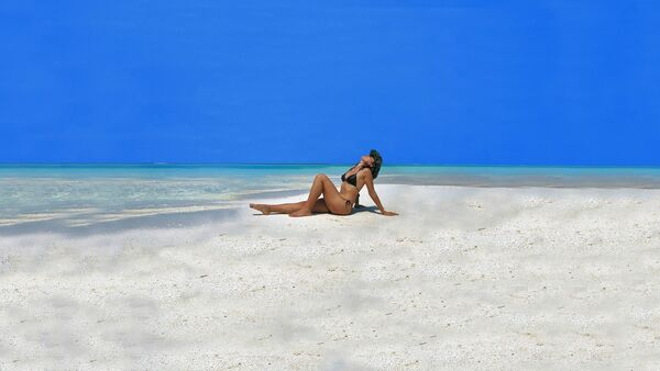 Una mujer toma sol en la playa - Sputnik Mundo