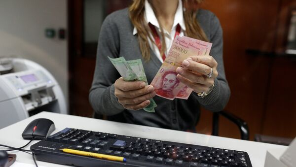 A bank teller counts bolivar banknotes at a Banco de Venezuela branch in Caracas - Sputnik Mundo