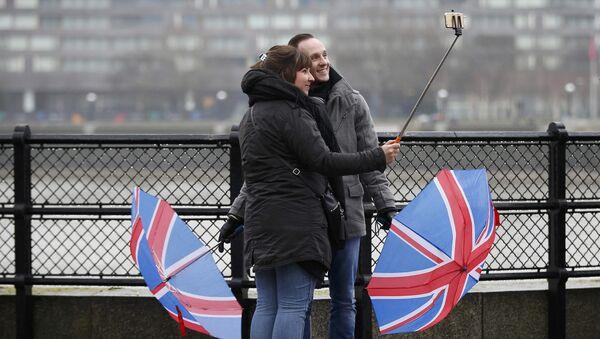 Turistas con paraguas en el color de la bandera del Reino Unido - Sputnik Mundo