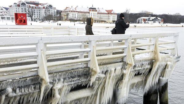 People walk along ice covered pier in Sopot, Poland - Sputnik Mundo