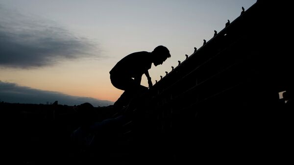 A migrant jumps to cross the U.S. Mexico border fence in Tijuana, Mexico, Thursday, Sept. 11, 2008. - Sputnik Mundo
