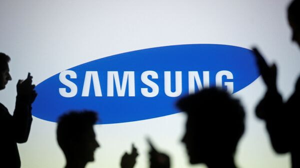 People are silhouetted as they pose with mobile devices in front of a screen projected with a Samsung logo, in this illustration picture - Sputnik Mundo