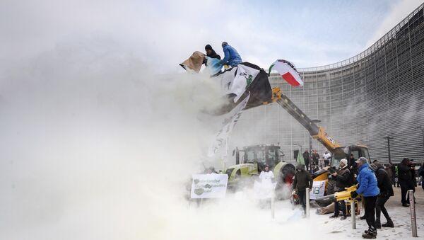 Granjeros rociando leche en polvo frente a la sede de la Consejo de la Unión Europea - Sputnik Mundo