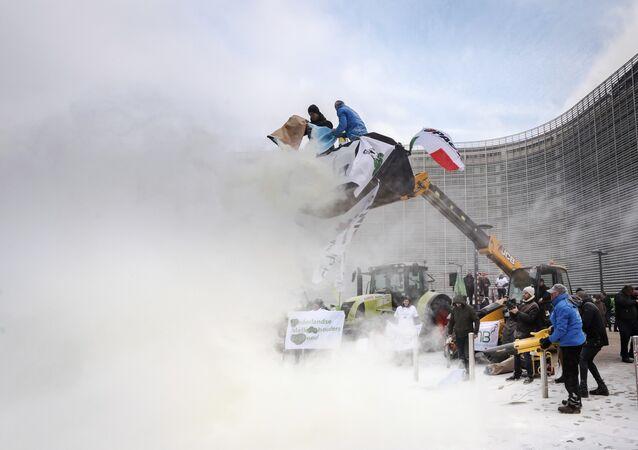 Granjeros rociando leche en polvo frente a la sede de la Consejo de la Unión Europea