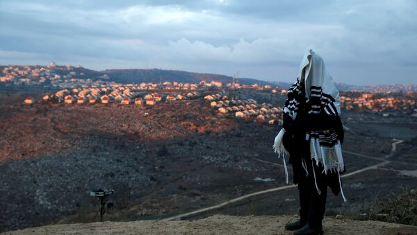 A Jewish man covered in a prayer shawl, prays in the Jewish settler outpost of Amona in the occupied West Bank December 18, 2016 - Sputnik Mundo