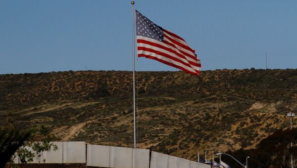 A U.S. flag is seen next to a section of the wall separating Mexico and the United States, in Tijuana, Mexico, January 28, 2017 - Sputnik Mundo