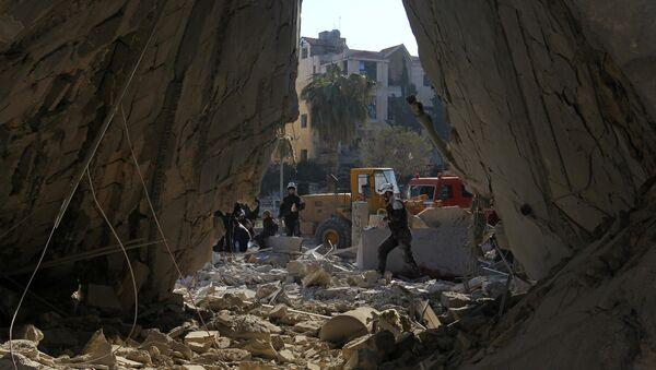 Civil defense members work at a site hit by airstrikes in the rebel-held city of Idlib, Syria - Sputnik Mundo