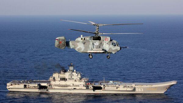 Un Ka-29, con el Almirante Kuznetsov de fondo, en el Mediterráneo - Sputnik Mundo