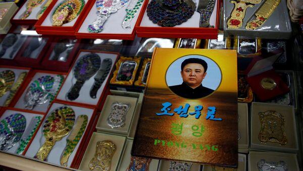 Un álbum de sellos con un retrato del difunto líder norcoreano Kim Jong-il en una exposición en una tienda de suvenires en Dandong - Sputnik Mundo