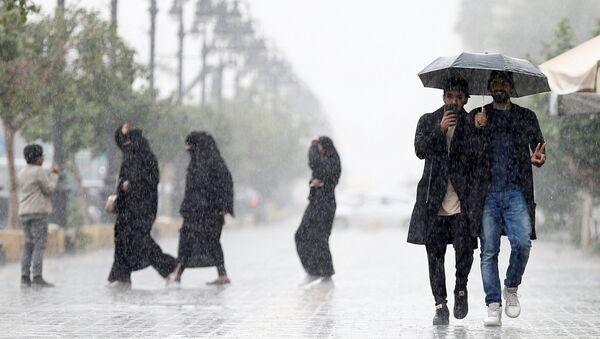 La gente bajo la lluvia en una calle de Riad - Sputnik Mundo