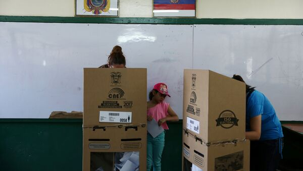 A girl looks on as women cast their votes during the presidential election at a school-turned-polling station in Quito, Ecuador - Sputnik Mundo