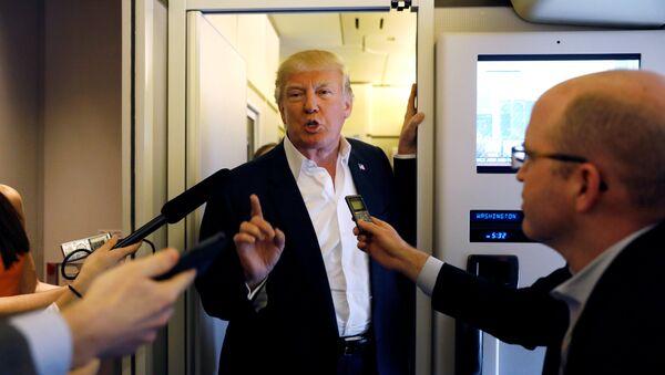 U.S. President Donald Trump speaks with reporters aboard Air Force One - Sputnik Mundo