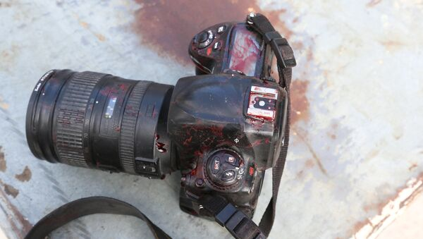 ATTENTION EDITORS - VISUALS COVERAGE OF SCENES OF DEATH OR INJURY - The blood stained camera of a photojournalist is seen after a secondary explosion in front of Dayah hotel in Somalia's capital Mogadishu - Sputnik Mundo