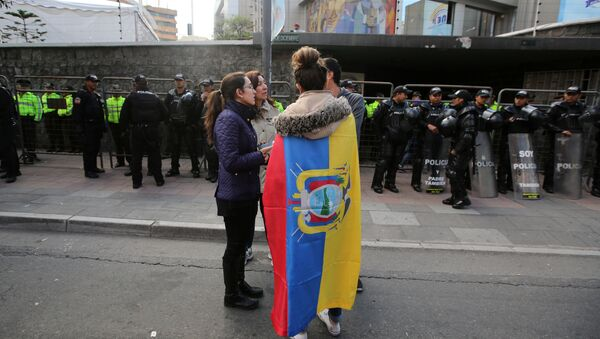 A woman wrapped in a national flag stands outside the electoral council (CNE) headquarters as leftist government candidate Lenin Moreno was set for victory but results still coming in meant he may face a runoff with CREO candidate Guillermo Lasso, in Quito - Sputnik Mundo