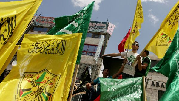 Palestinian supporters of Hamas Islamist movement and of Fatah party wave their faction's flags during a rally to support the Palestinian political unity deal, in the West Bank city of Jenin. (File) - Sputnik Mundo