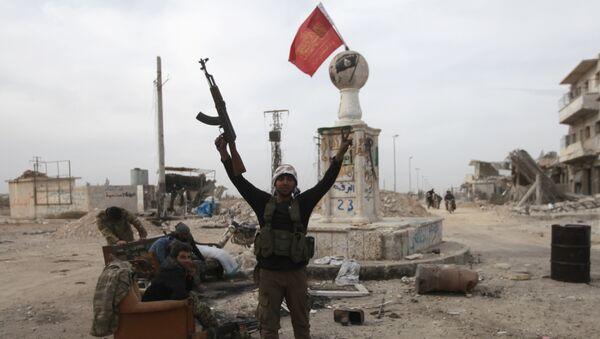 Un combatiente rebelde cerca de edificios dañados en la ciudad siria de al-Bab - Sputnik Mundo