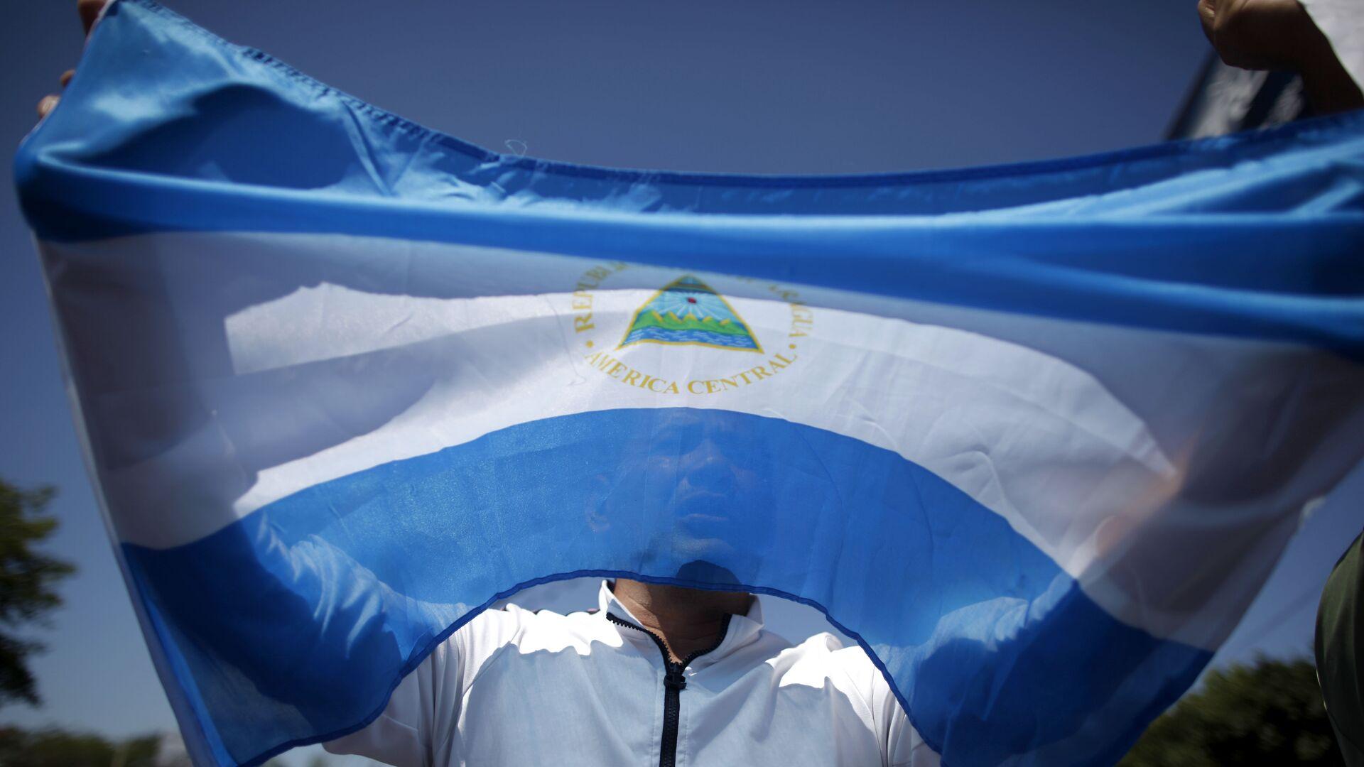 A man holds up a Nicaraguan flag during a demonstration against the presidential candidacy of Nicaragua's President Daniel Ortega in Managua, Nicaragua, Sunday, Feb 20, 2011.  - Sputnik Mundo, 1920, 17.06.2021
