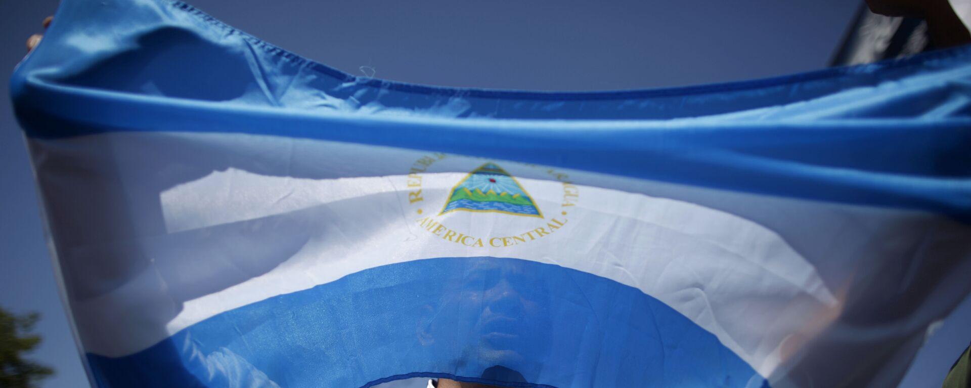 A man holds up a Nicaraguan flag during a demonstration against the presidential candidacy of Nicaragua's President Daniel Ortega in Managua, Nicaragua, Sunday, Feb 20, 2011.  - Sputnik Mundo, 1920, 23.07.2021