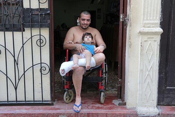 Кубинец с ребенком в районе Старая Гавана - Sputnik Mundo