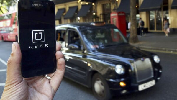 A photo illustration shows the Uber app logo displayed on a mobile telephone, as it is held up for a posed photograph in central London, Britain August 17, 2016. - Sputnik Mundo