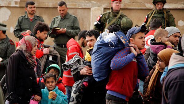 Grupo de personas abandonando Homs - Sputnik Mundo