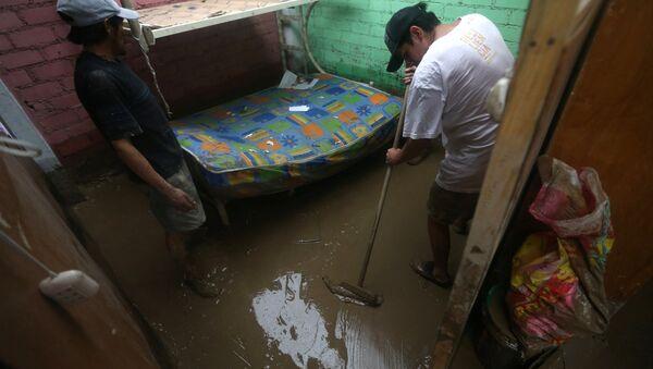 Peruanos limpian sus casa tras las inundaciones - Sputnik Mundo