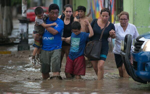 Peruanos cruzan una calle inundada en Trujillo - Sputnik Mundo