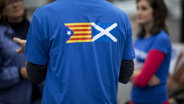 David Aguilar who is visiting Scotland from Catalonia to support the Scottish independence referendum, wears a t-shirt printed with a design showing an estelada Catalan pro-independence flag, left, next to a Scottish Saltire flag as he speaks to passersby in Edinburgh, Scotland, Thursday, Sept. 18, 2014 - Sputnik Mundo