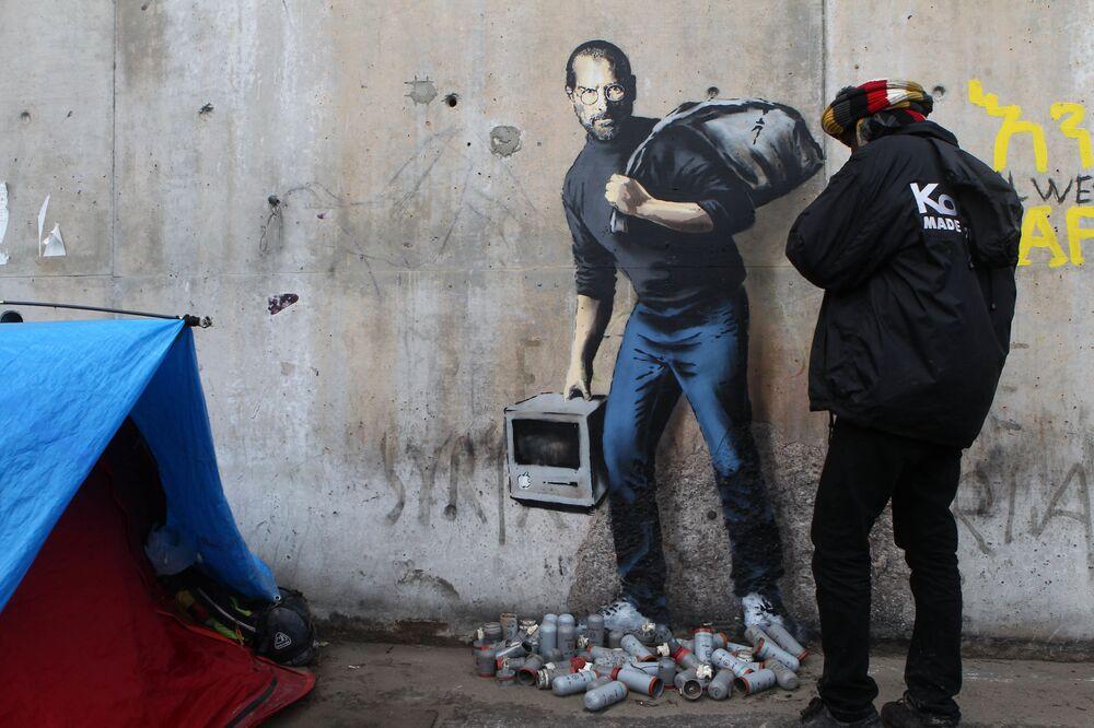 Grafiti del artista Banksy que representa a Steve Jobs en el muro de un campo de refugiados en Francia