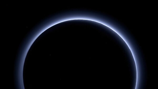 This image released by NASA on Thursday, Oct. 8, 2015 shows a haze layer surrounding Pluto, photographed by the New Horizons spacecraft. This image was generated by software that combines information from blue, red and near-infrared images to replicate the color a human eye would perceive as closely as possible. On Friday, Oct. 28, 2016, NASA said the spacecraft has sent back the last bit of data collected from its July 14, 2015 flyby. It took more than five hours for the image to reach Earth from NASA's New Horizons spacecraft, some 3 billion miles away. - Sputnik Mundo