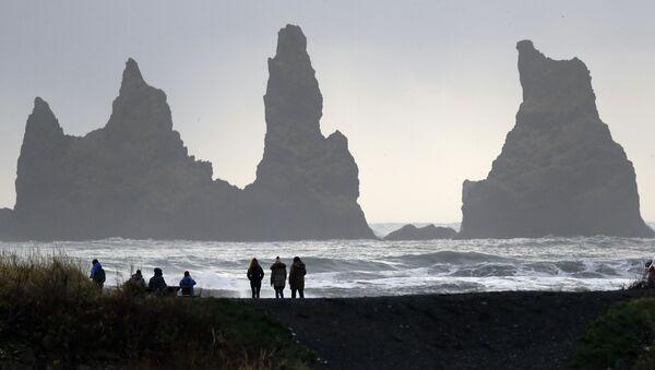 People walk on the black sanded beach in Vik, Iceland, near the Volcano Katla - Sputnik Mundo