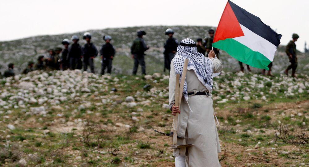 Hombre sujeta bandera palestina frente a militares israelís (archivo)
