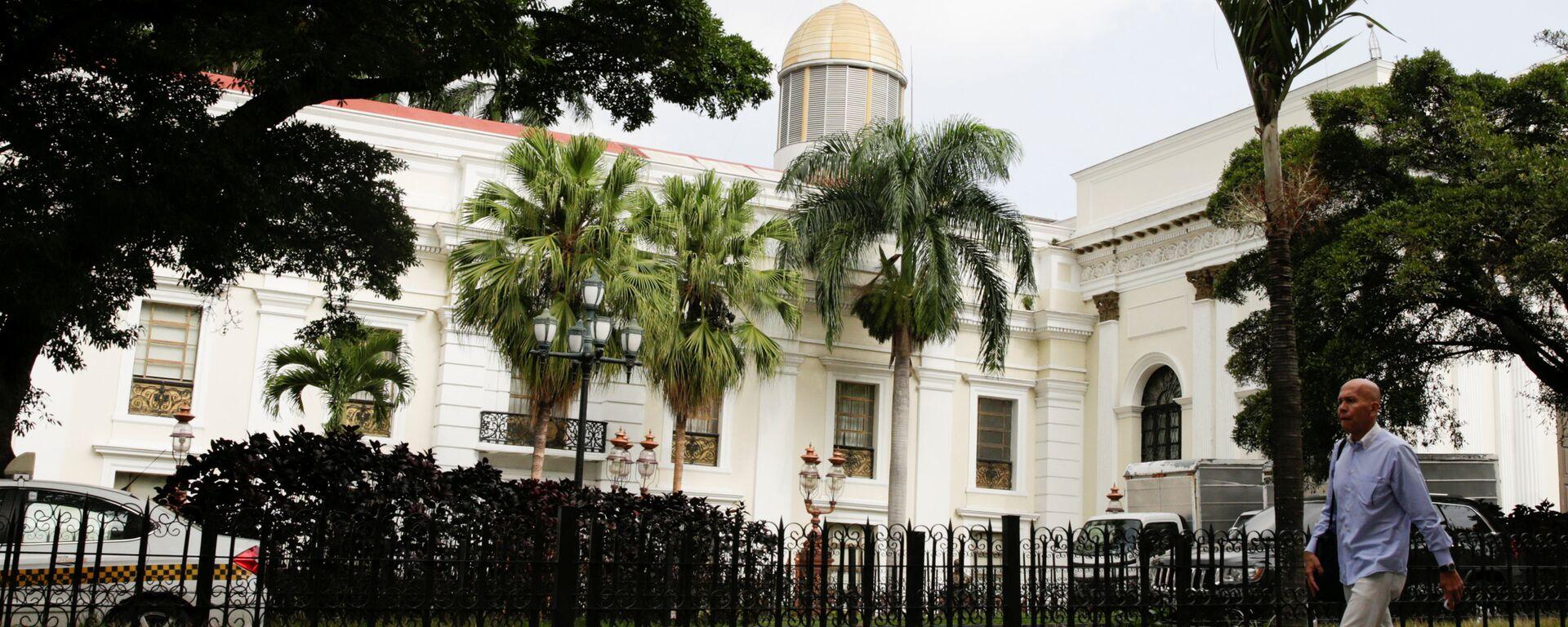 A man walks past the building of the National Assembly in Caracas, Venezuela - Sputnik Mundo, 1920, 17.08.2021