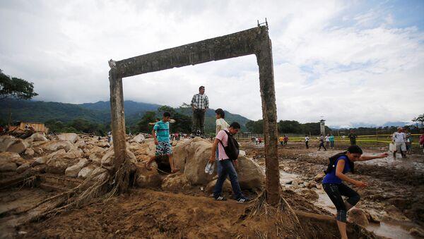 Personas caminan en una zona destruida tras las inundaciones y los deslizamientos de tierra causados por fuertes lluvias en Mocoa, Colombia - Sputnik Mundo