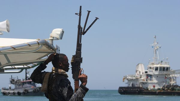 A maritime policeman on a tag-boat guards oil tanker Aris-13, which was released by pirates, as it sails to dock on the shores of the Gulf of Aden in the city of Bosasso, northern Somalia's semi-autonomous region of Puntland, March 19, 2017 - Sputnik Mundo