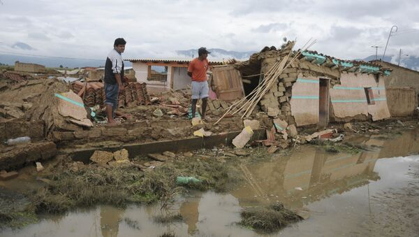Two men look at collapsed houses after a flood in Churusi-Punata in Cochabamba, Bolivia, Friday, Feb. 7, 2014. The latest report released by Bolivia's Ministry of Defense said the storms plaguing Bolivia since last September has left a momentary balance of dozens of deaths and thousands of families evacuated from their homes. - Sputnik Mundo